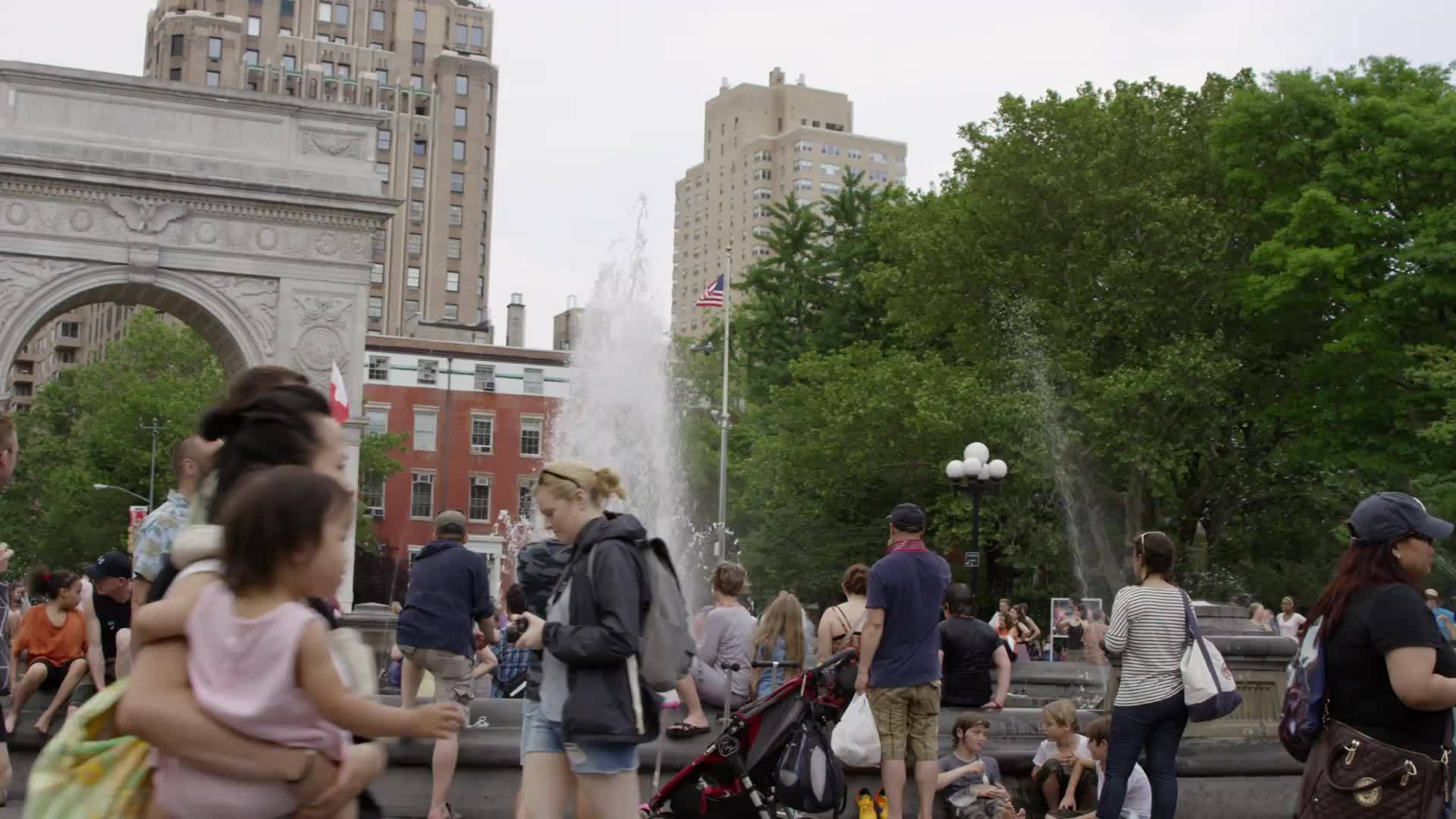 people walking in Washington Square Park by Tisch Fountain in summer in slow motion - famous landmark arch