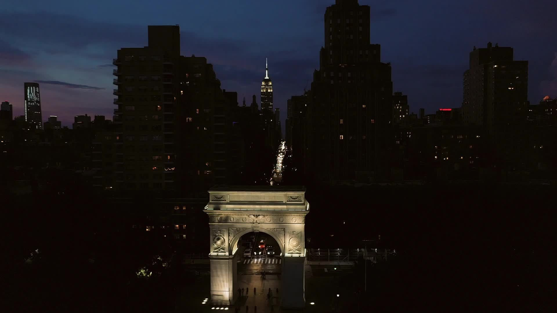 aerial moving toward Empire State building over arch in Washington Square Park at night NYC