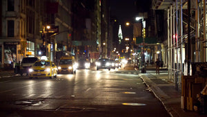 Chrysler Building in distance view from Downtown Broadway in SoHo at night, cars and taxis driving in Manhattan NYC