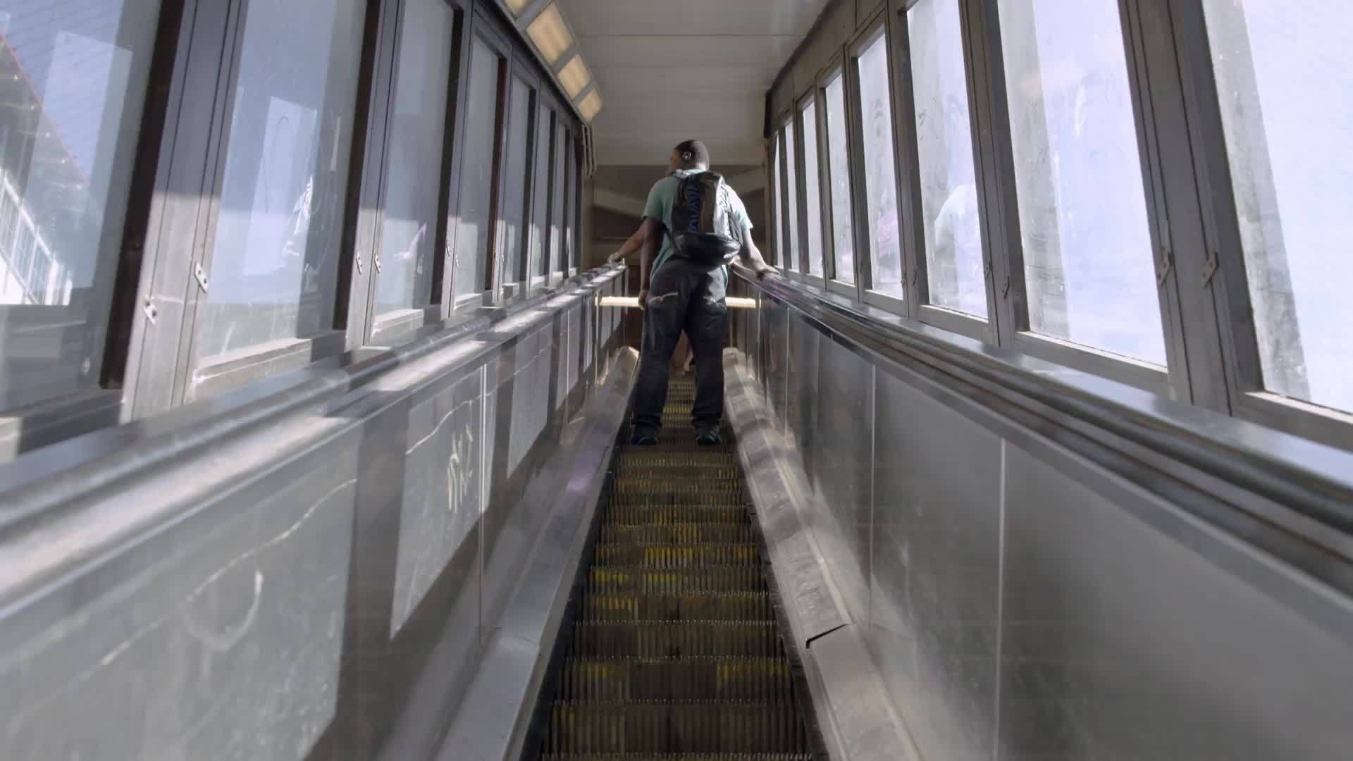 up escalator in 125th street subway station in Harlem - kid with backpack riding escalator going up
