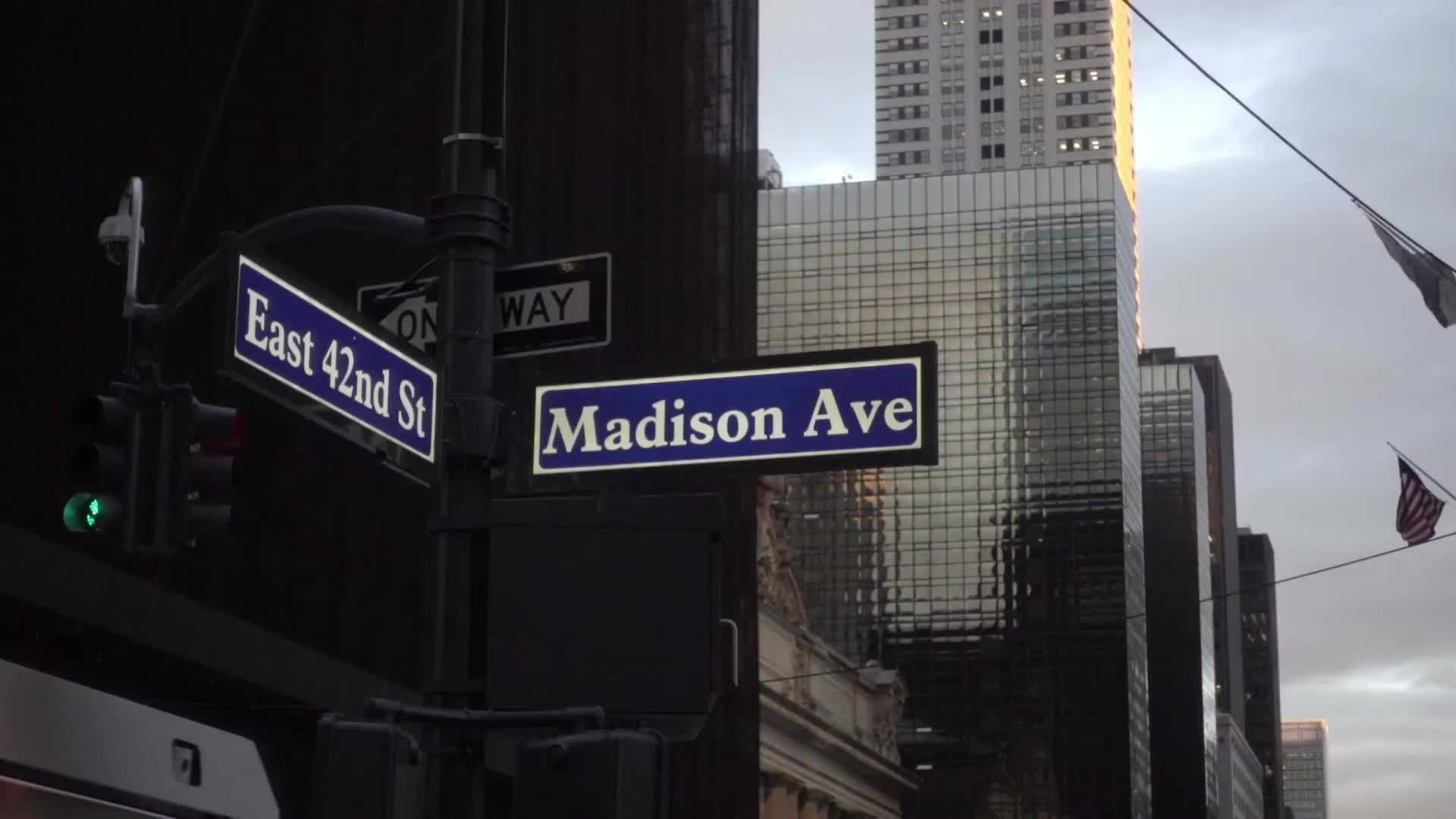 East 42nd Street and Madison Ave sign on street corner intersection, zooming out to busy crowded street with Chrysler Building in wide shot, Manhattan NYC 1080p HD