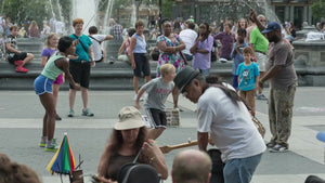 blonde kid playing Double Dutch in Washington Square Park on summer day