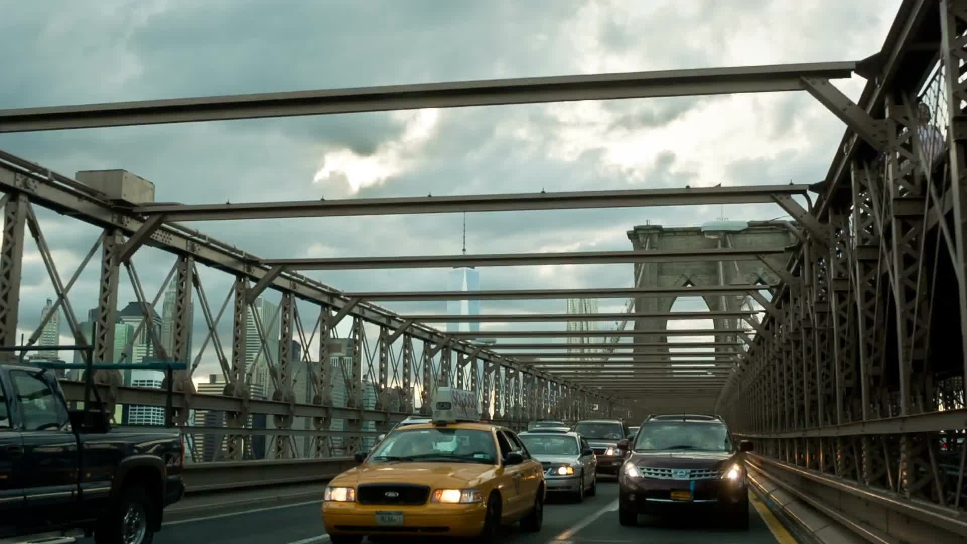 taxi cab crossing Brooklyn Bridge - cars driving in traffic on cloudy day in NYC
