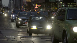 Midtown Manhattan street with bright headlights on cars in traffic in early evening, slow motion Manhattan NYC