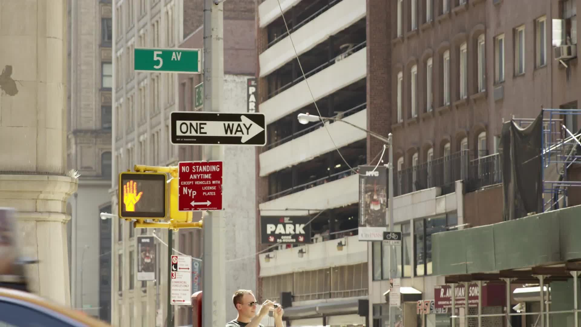 5th Avenue sign with one way arrow - taxi cab driving down Fifth Ave on summer day in Manhattan NYC