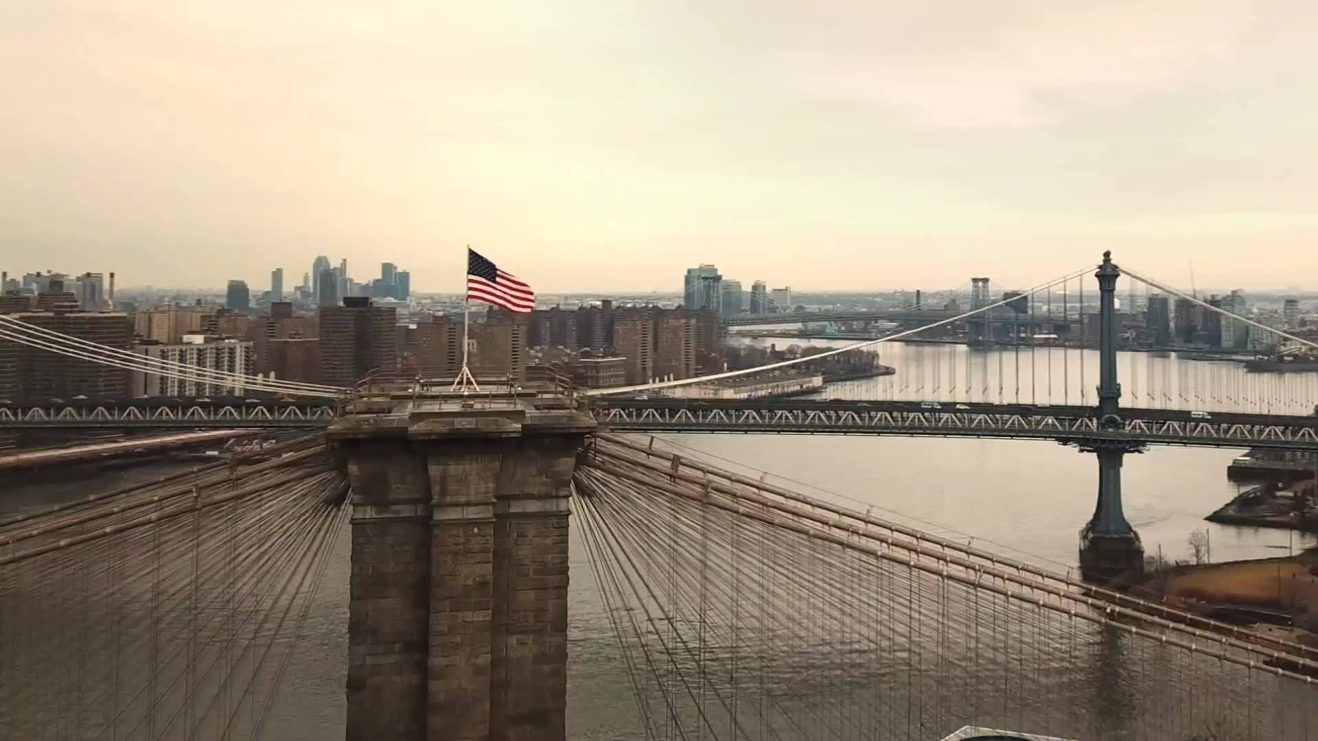 Brooklyn Bridge with American flag aerial circling toward Manhattan skyline with Freedom Tower in 1080 HD