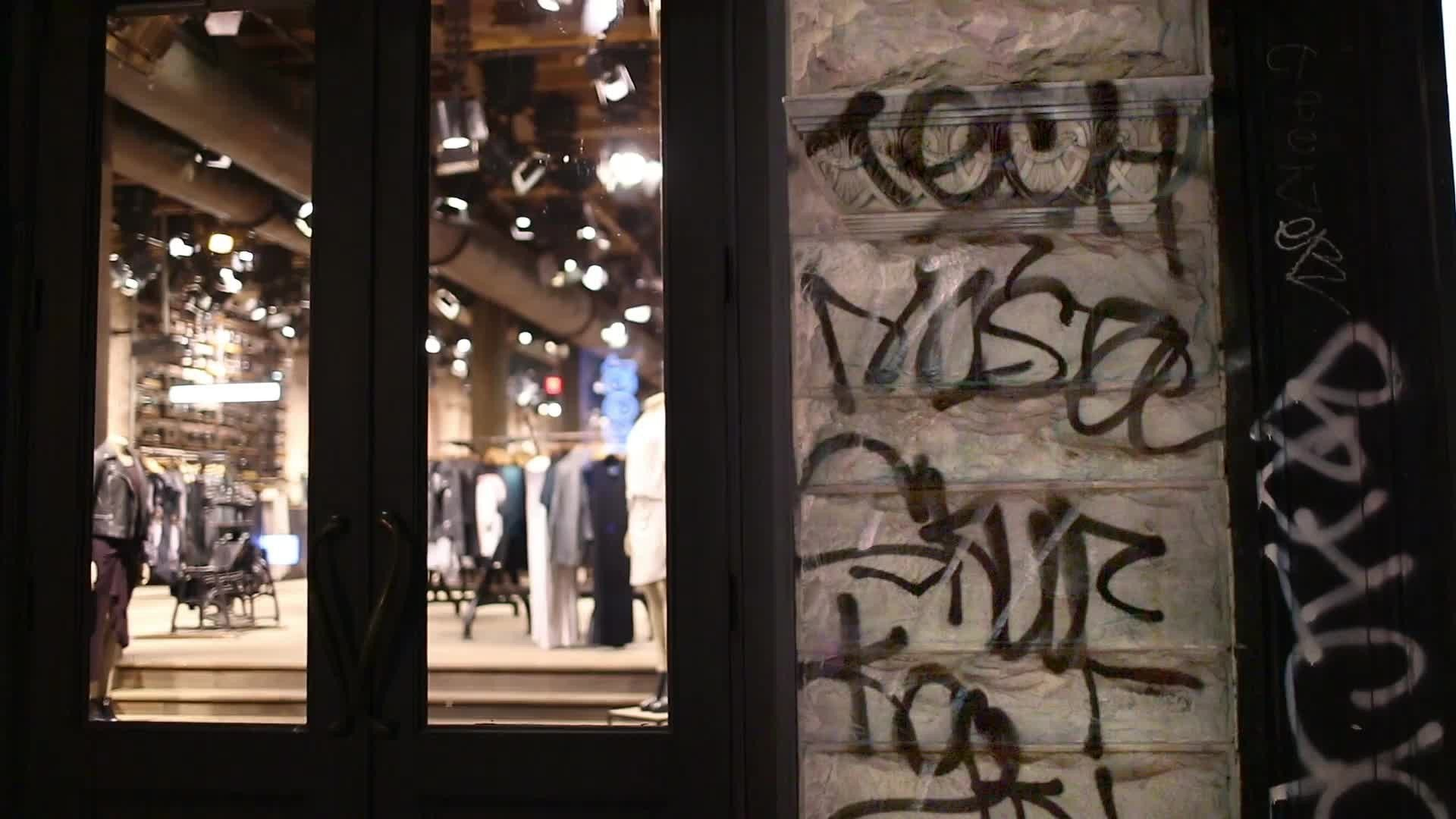 graffiti written on entrance of clothing store at night on Broadway with audio in NYC