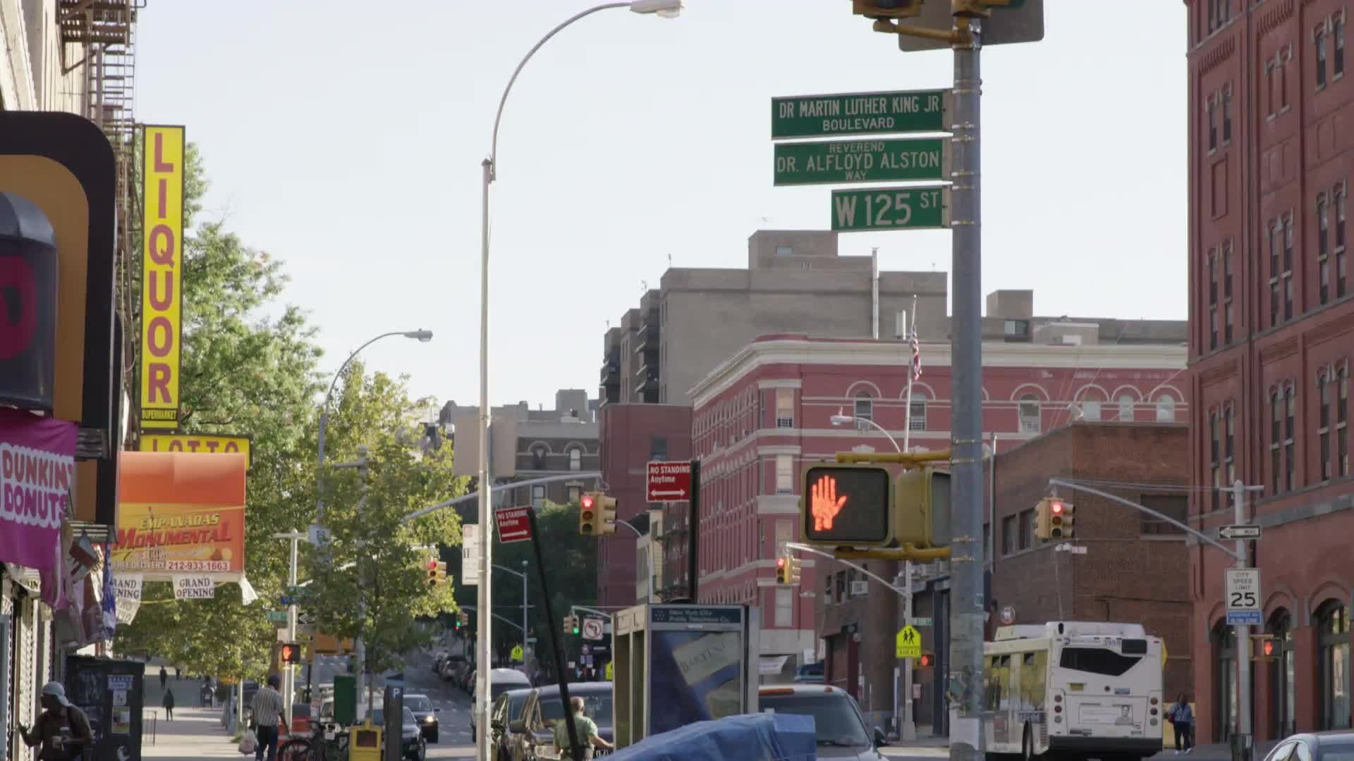 125th Street sign - cars and bus driving in street in Harlem - uptown