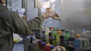 man taking hot dog from window of food cart in New York City NYC