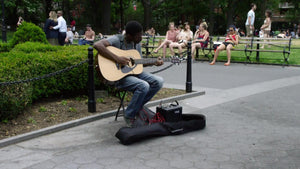 man playing guitar in Washington Square Park in New York City