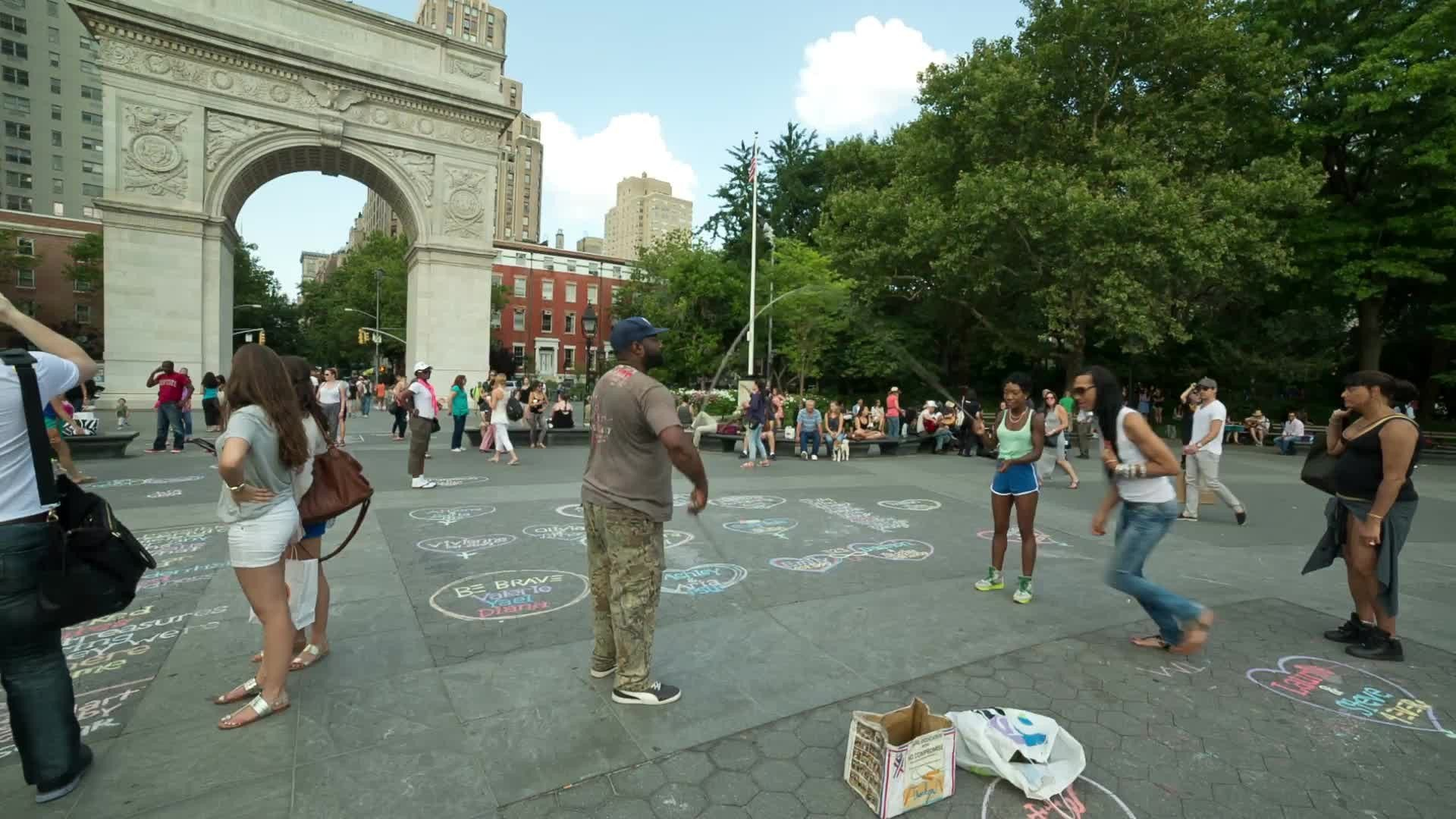trans woman playing Double-Dutch in Washington Square Park on summer day in NYC