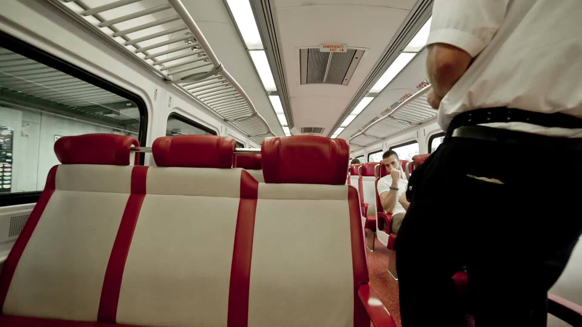 conductor collecting and punching tickets on Metro North - train interior with red and white seats