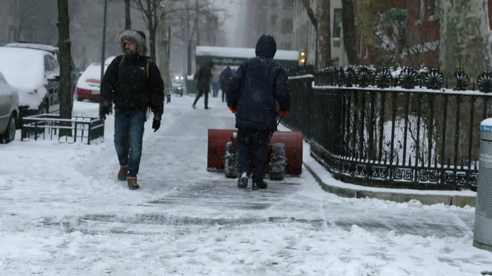 man plowing snow with snow plow in winter blizzard snowstorm - snowing in slow motion in Manhattan