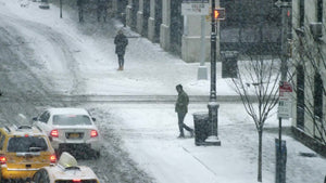 man crossing street in winter blizzard snow storm, snowing on street in far shot slow motion 4K