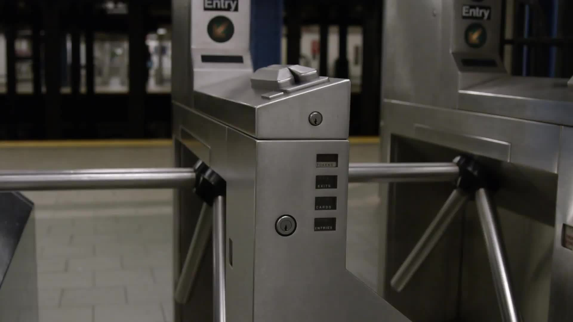 tracking shot of turnstiles in empty subway station in NYC