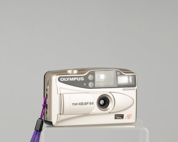 The Olympus Trip XB AF44 is a compact 35mm film camera featuring a 27mm wide-angle lens