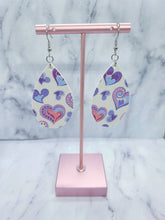 Load image into Gallery viewer, WHITE WITH PURPLE, BLUE, AND PINK HEARTS MAGNOLIA - FAUX LEATHER EARRINGS