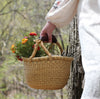 Mini Bolga basket in hand of child in woodland setting.
