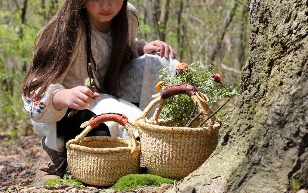 Young girl foraging sticks and flowers in her small bolga basket.