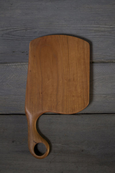 Handcrafted cherry wood cutting board with handle. American made gift.