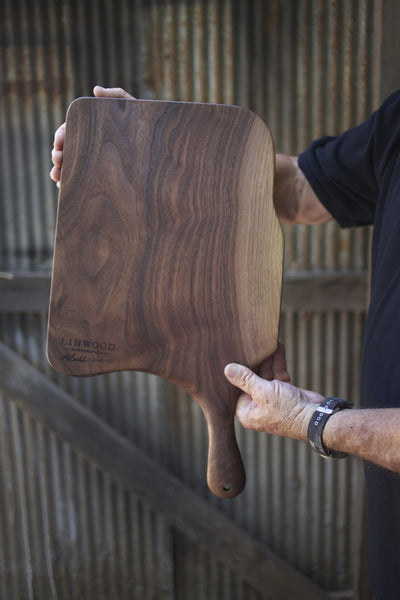 111. Black walnut wooden cutting board with handle and blonde streaks.