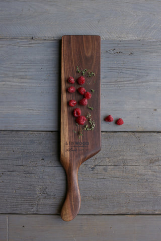 176. Handmade black walnut wooden cutting board with handle and blonde streak front angle.