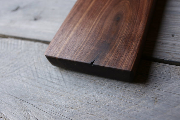 176. Handmade black walnut wooden cutting board with handle and blonde streak close angle.