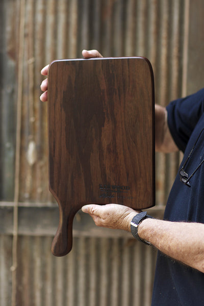 328. Handmade black walnut wood cutting board with a handle - held view 1