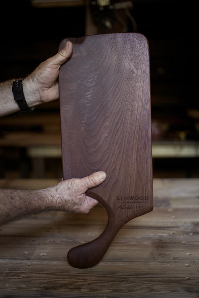 208. Handmade black walnut wood cutting board with handcrafted handle.