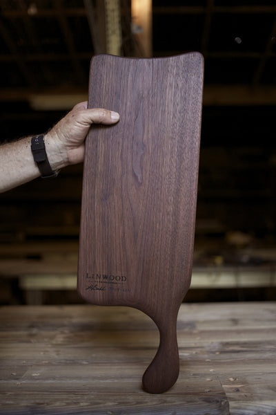 210. Handmade black walnut wood cutting board with handcrafted handle.