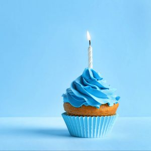 cupcake with blue frosting and a candle