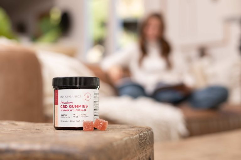 CBD Gummies in front of woman sitting on couch