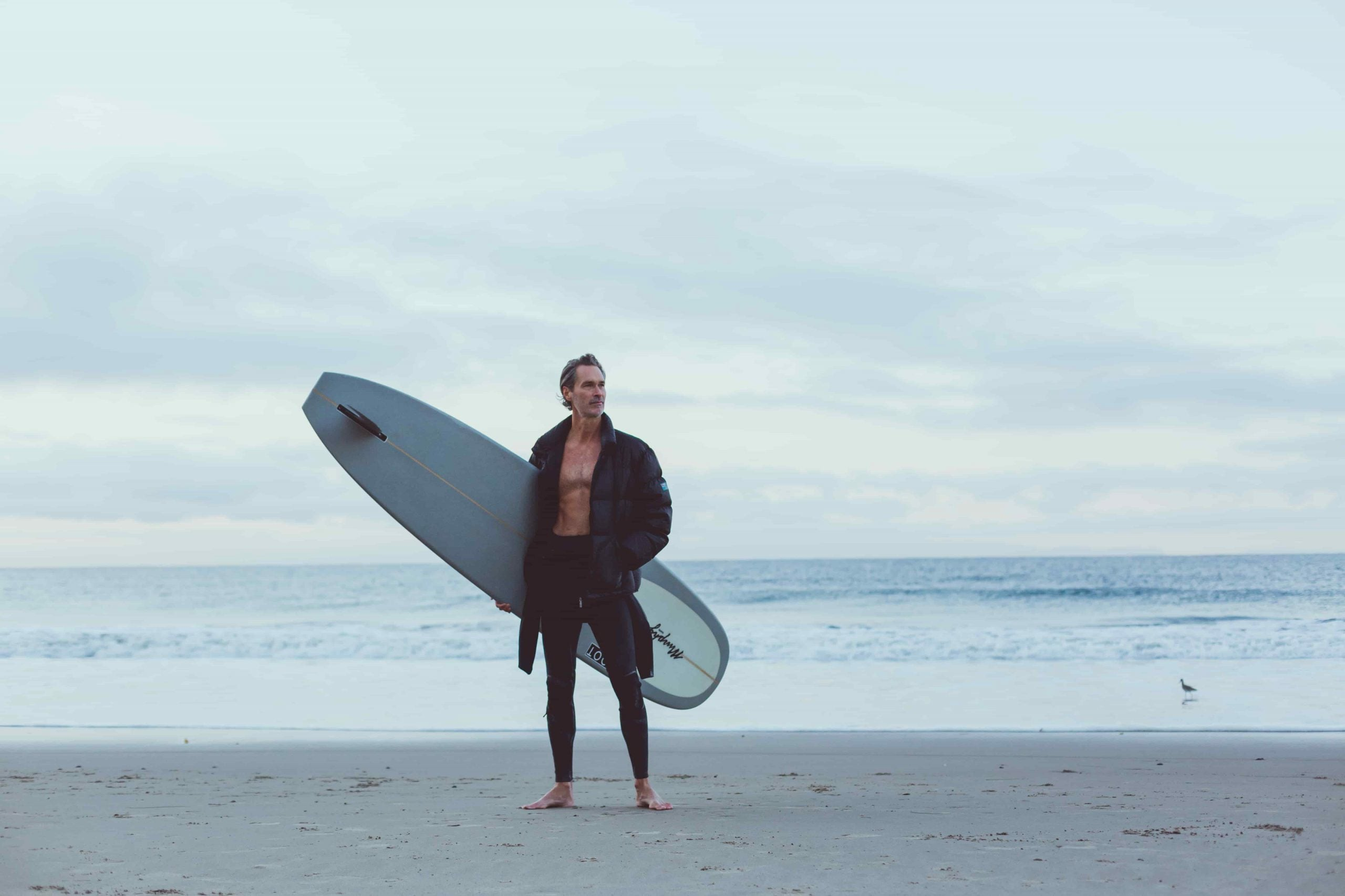 man holding surfboard in front of the ocean