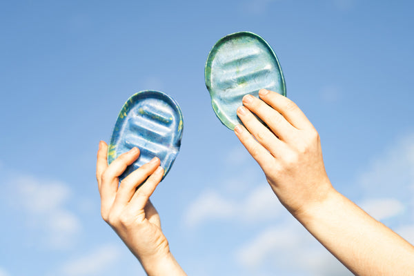 Two hands holding a soap dish each up to the sky, which is blue with some wispy clouds.