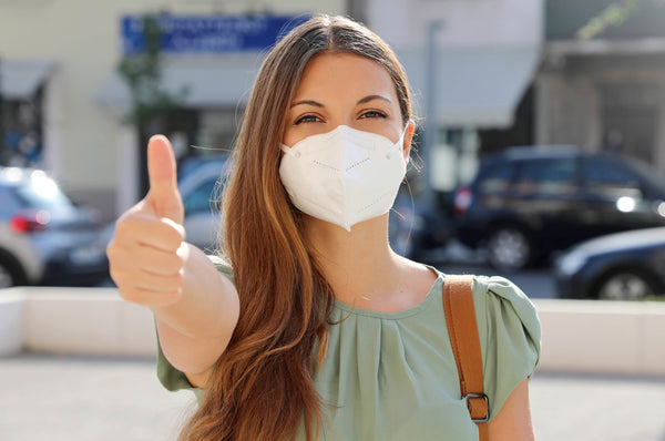Woman in KN95 mask giving thumbs up