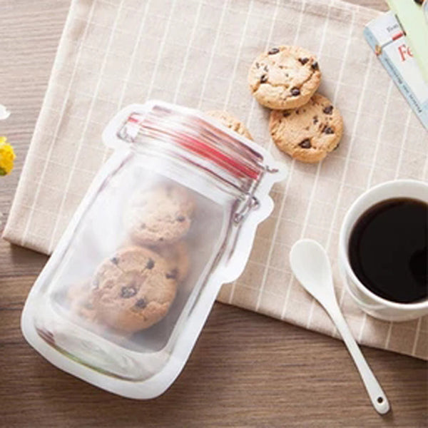 Medium size Mason Jar Bag with five chocolate chip cookies inside of it and 2 cookies outside of it.  Next to it is a spoon, a cup of coffee, and some books.  Everything is sitting on top of a tan napkin and a wood table.