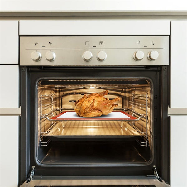 A whole chicken on top of the non-stick baking mat and a pan.  Placed on the middle shelf of an oven.