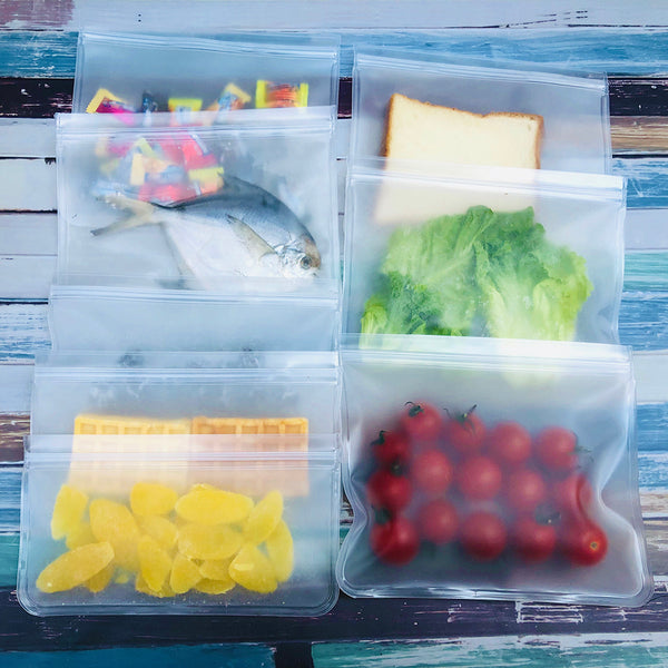 Eight reusable storage bags each with a different type of food or snack