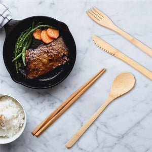 Bamboo knife, spoon, fork, and chopsticks next to a frying pan with meat and a bowl of rice