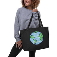 "A model wearing a gray top and black pants is holding onto a filled Black Stop Wasting, Start Reusing Tote Bag.  She is showing the front of the bag which has an image of the world and the words ""Stop Wasting, Start Reusing"" in the middle of the world."