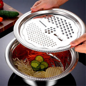 Someone is holding the grating lid over the colander & mixing bowl.  Inside are sliced up cucumbers, carrots, potatoes, & onions.  Next to it is a dark brown cutting board with full size vegetables on top.