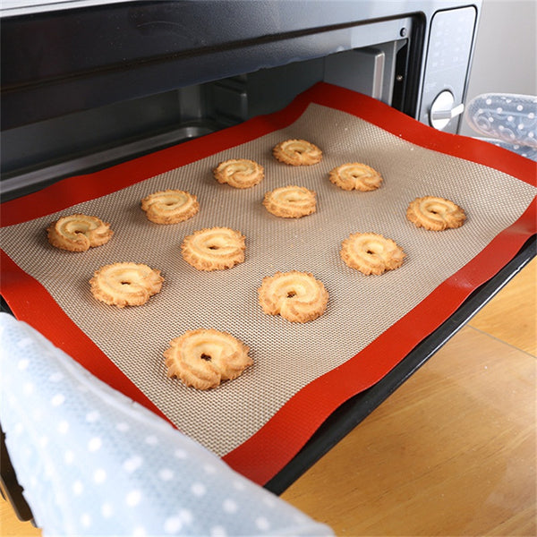 Someone putting a pan with a medium size Non-Stick Baking Mat and cookies into a countertop oven