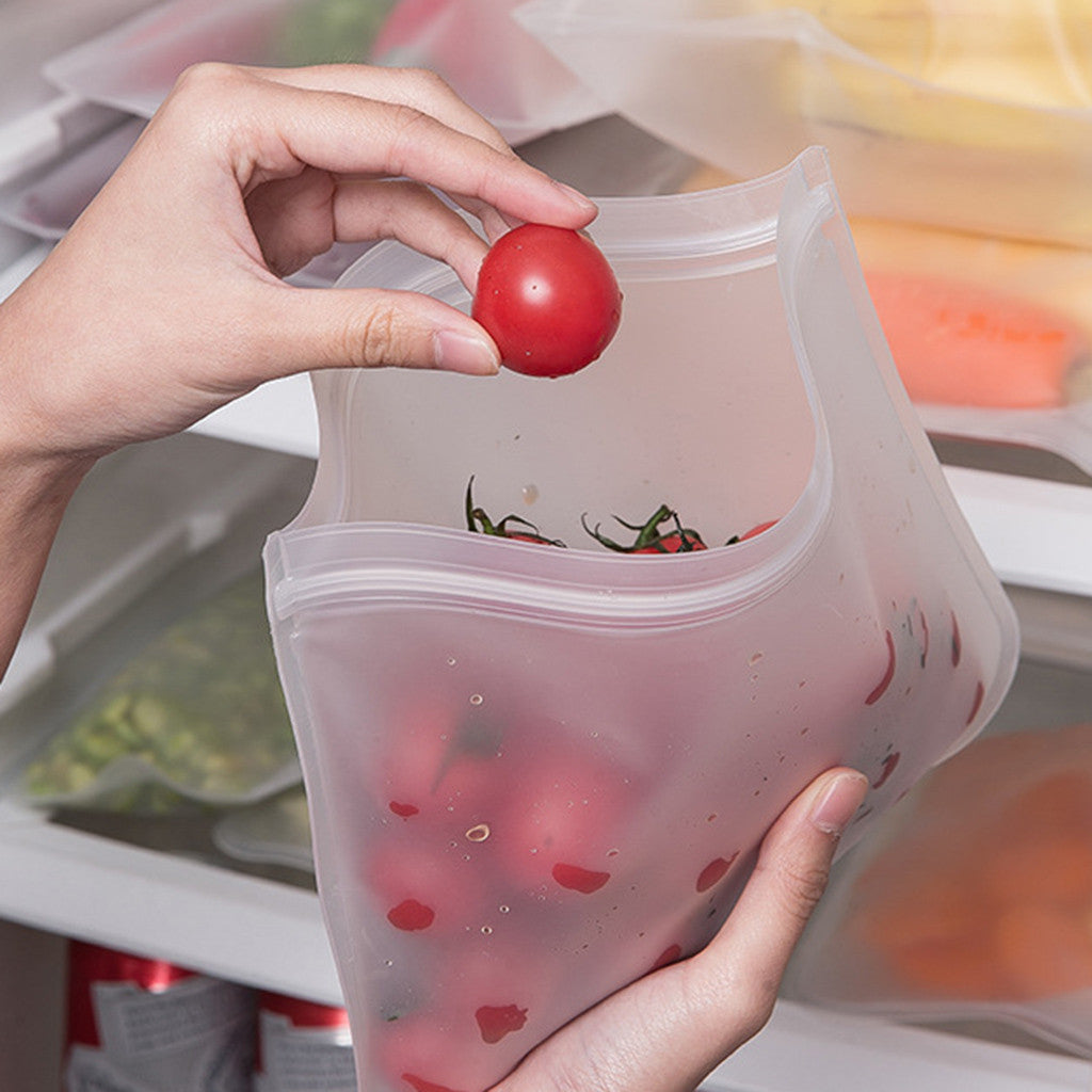 Someone is holding a Reusable Storage Bag (Flat) with cherries inside of it next to a fridge shelf.