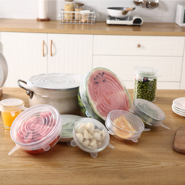 Wood countertop with eight Silicone Food Covers each on something different.  Some of the things include a cup of orange juice, a dish of cut up watermelon, a medium size pot, a bowl of onions, a bowl with orange slices, half of a watermelon, & a jar of peas.
