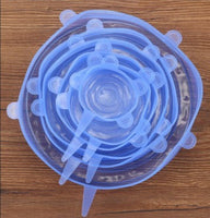 Silicone Food Cover Set (Blue) sitting on a wood table.  Going from big to small, the different sizes are placed inside the other.  6 pieces.