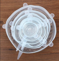 Silicone Food Cover Set (Transparent) sitting on a wood table.  Going from big to small, the different sizes are placed inside the other.  6 pieces.
