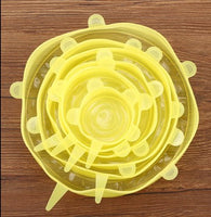 Silicone Food Cover Set (Yellow) sitting on a wood table.  Going from big to small, the different sizes are placed inside the other.  6 pieces.