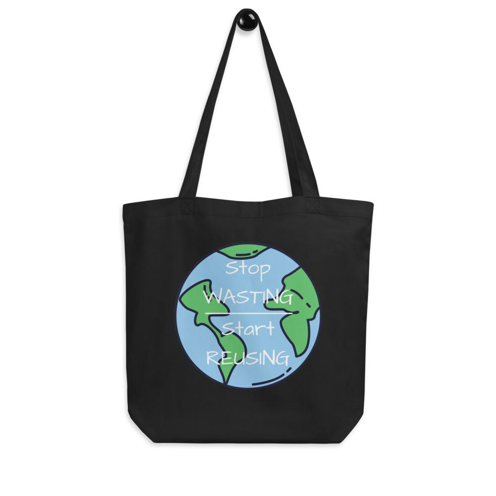 "Black Stop Wasting, Start Reusing Tote Bag hanging on a white wall.  It is showing the front side of the bag which has an image of the world and the words ""Stop Wasting, Start Reusing"" in the middle of the world."