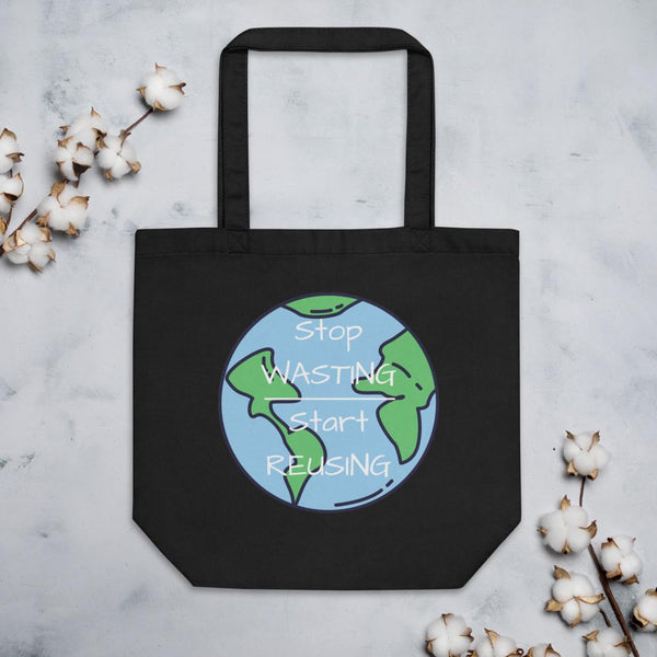 "Front of the Small Black Tote Bag lying on a gray granite table.   On it is an image of the world with the words ""Stop Wasting, Start Reusing"" in the middle of the world.  Above & below the tote bag are flowers."