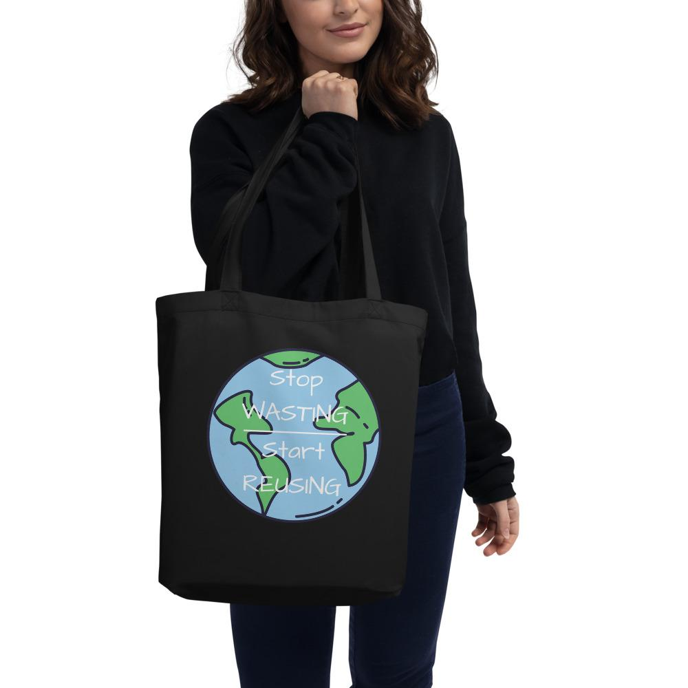 "A model wearing a black top and dark blue jeans holding onto a filled Black Stop Wasting, Start Reusing Tote Bag.  She is showing the front of the bag which has an image of the world and the words ""Stop Wasting, Start Reusing"" in the middle of the world."